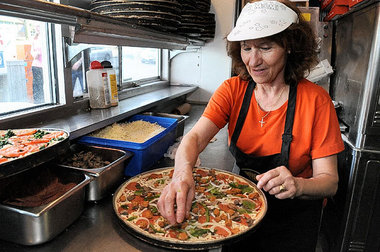 Elli Darmoyslis, who has worked for 41 years at the Varsity, prepares a Varsity special pizza at the SU Hill institution Tuesday afternoon